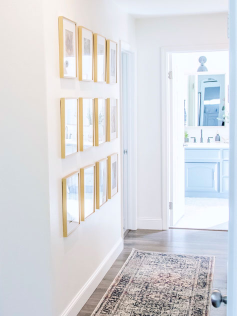 wall gallery of gold metal frames in white hallway