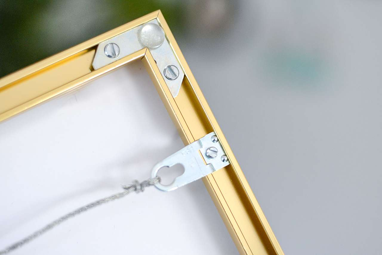Hanging wire and back of a gold metal frame