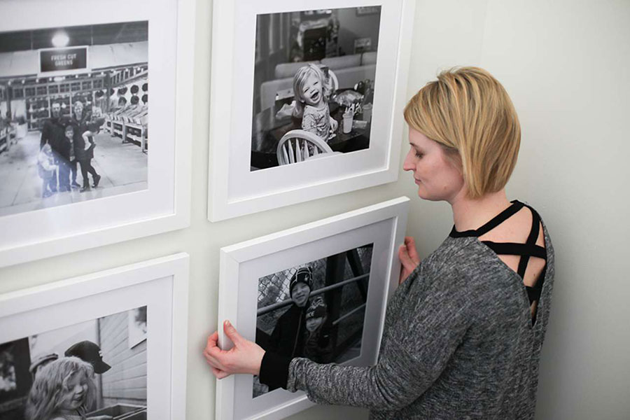 Woman hanging up picture frames on wall