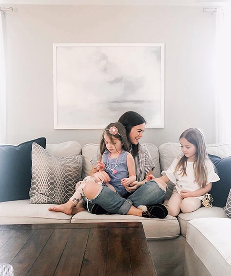 framed art on wall behind mother with two daughters on beige couch