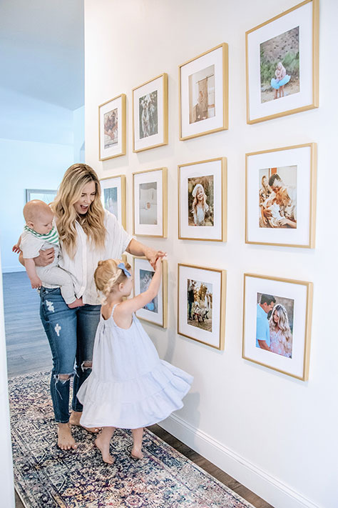smiling mother with two children with gold frames hanging in hallway