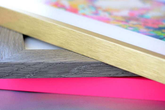 Gold and pink metal picture frames with gray wood picture frame