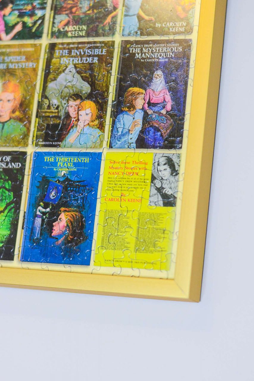 Close-up of gold puzzle frame with Nancy Drew book covers