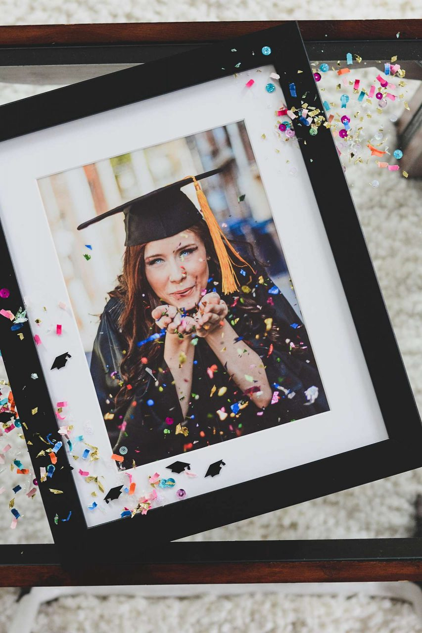 Framed graduation photo gift blowing confetti on table