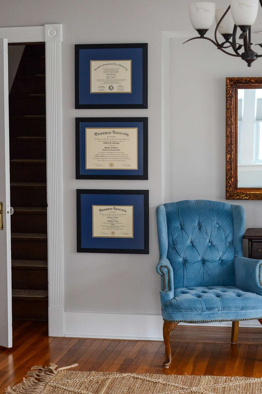 Framed diplomas on a wall with chair