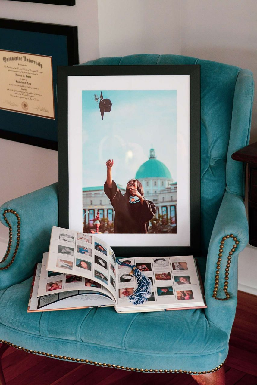 Framed graduation gift photo with yearbook and tassel on chair