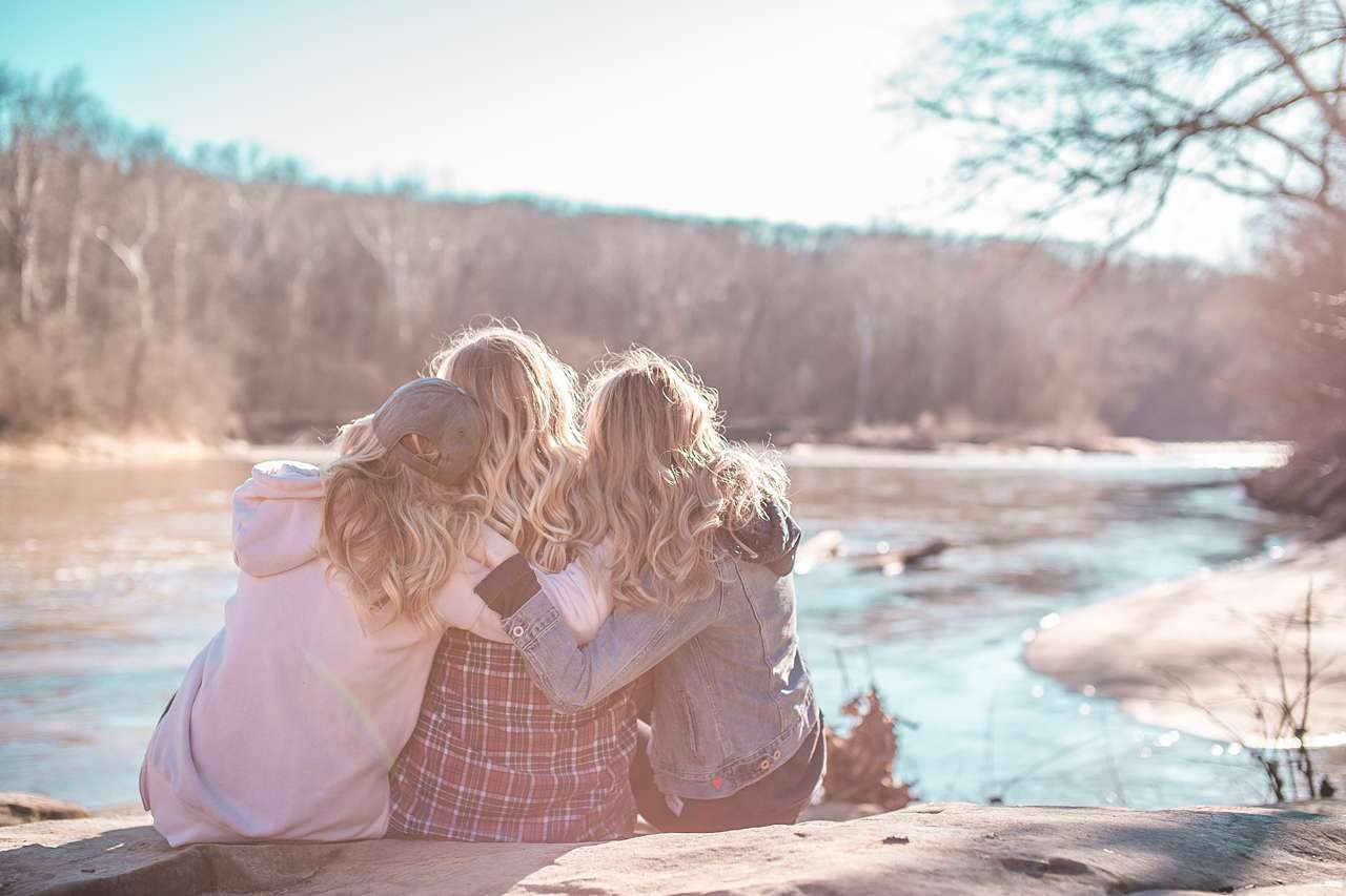 Three friends photo admiring creek in winter