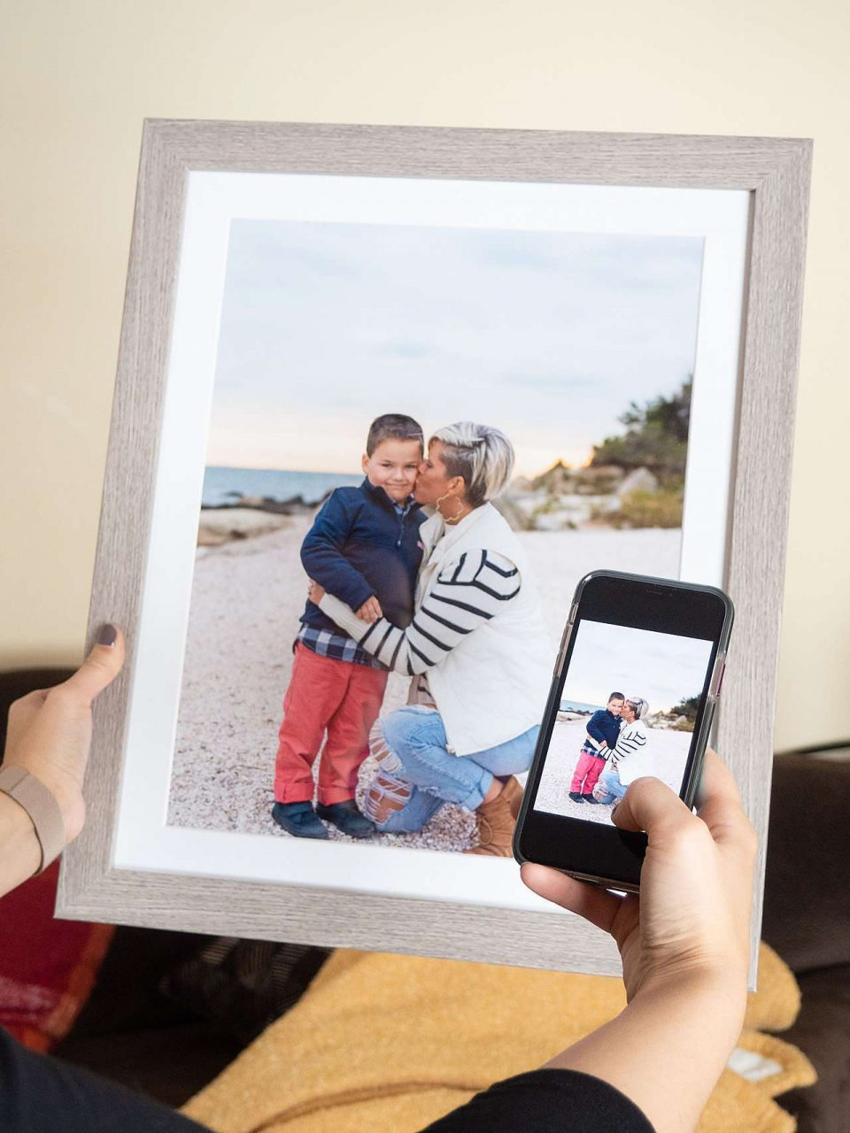Phone taking picture of framed photo of mother and son