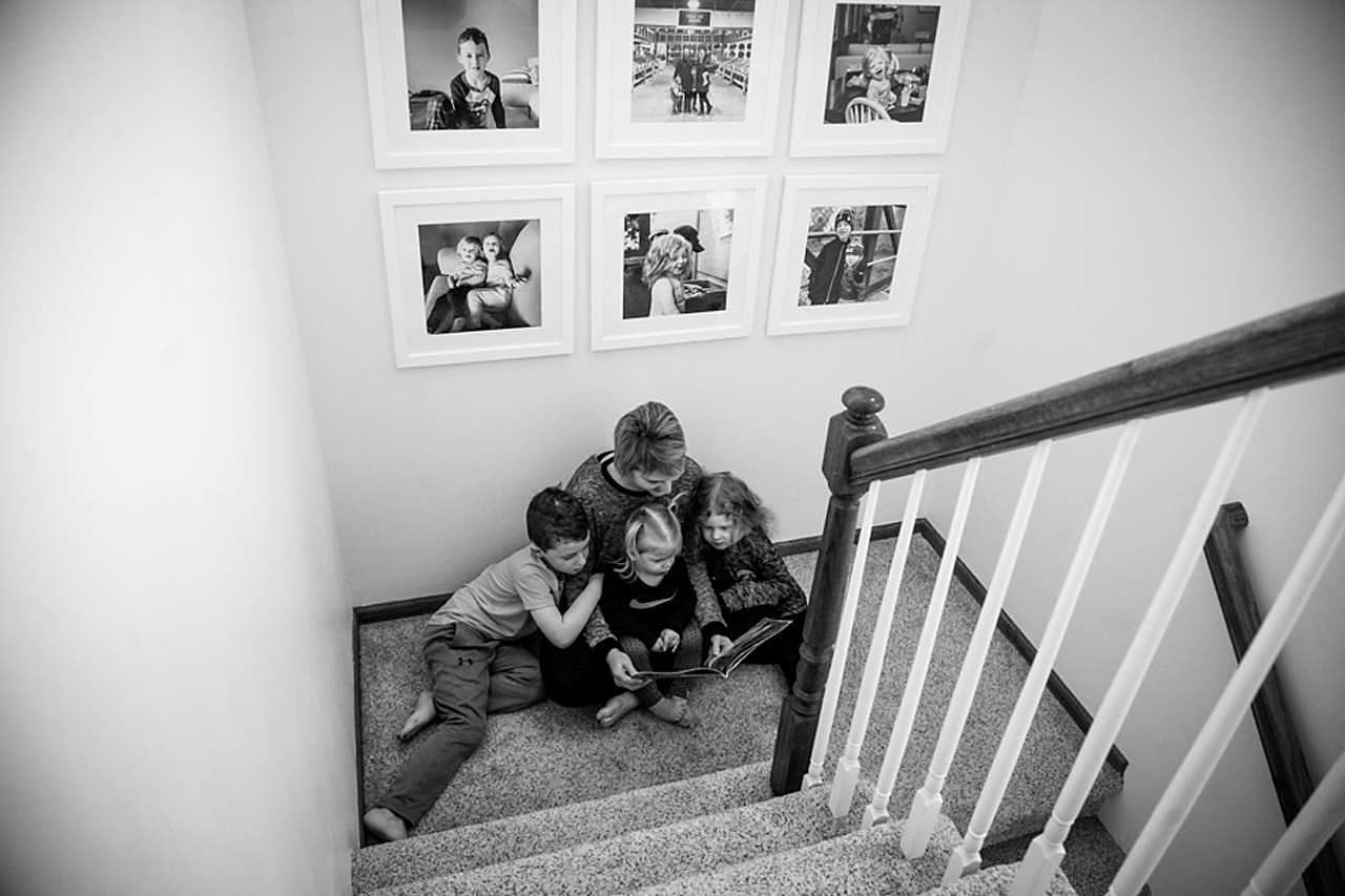 Mom reading book to kids at bottom of stairs under framed family photos