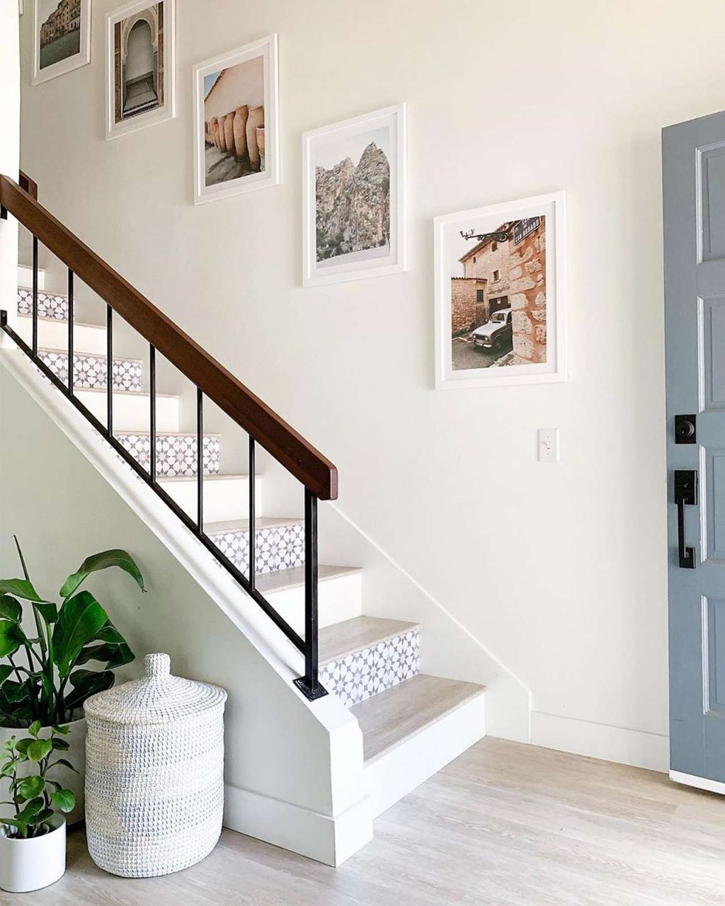White picture frames on wall with staircase