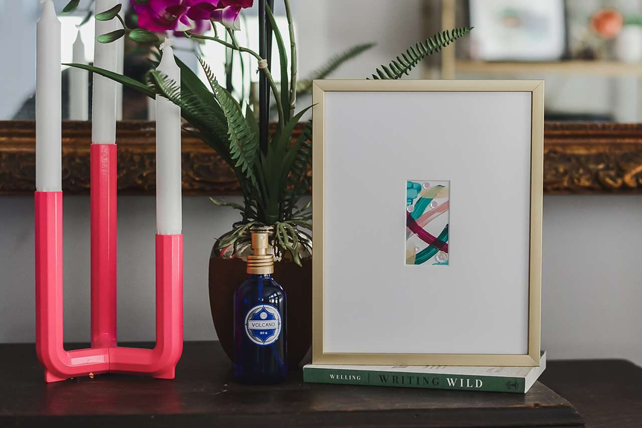 Art with white matting in gold frame next to candle and flower