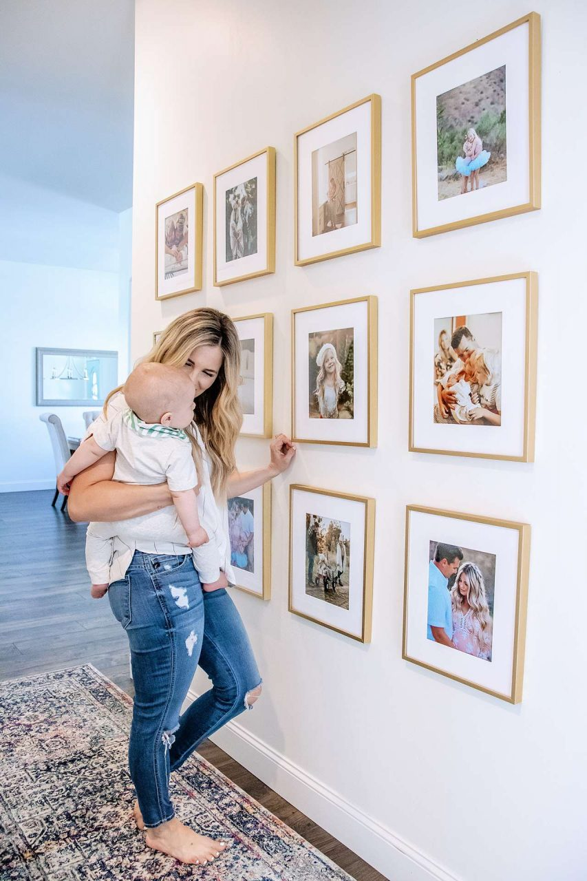 Gold gallery wall of family photos with mother holding infant