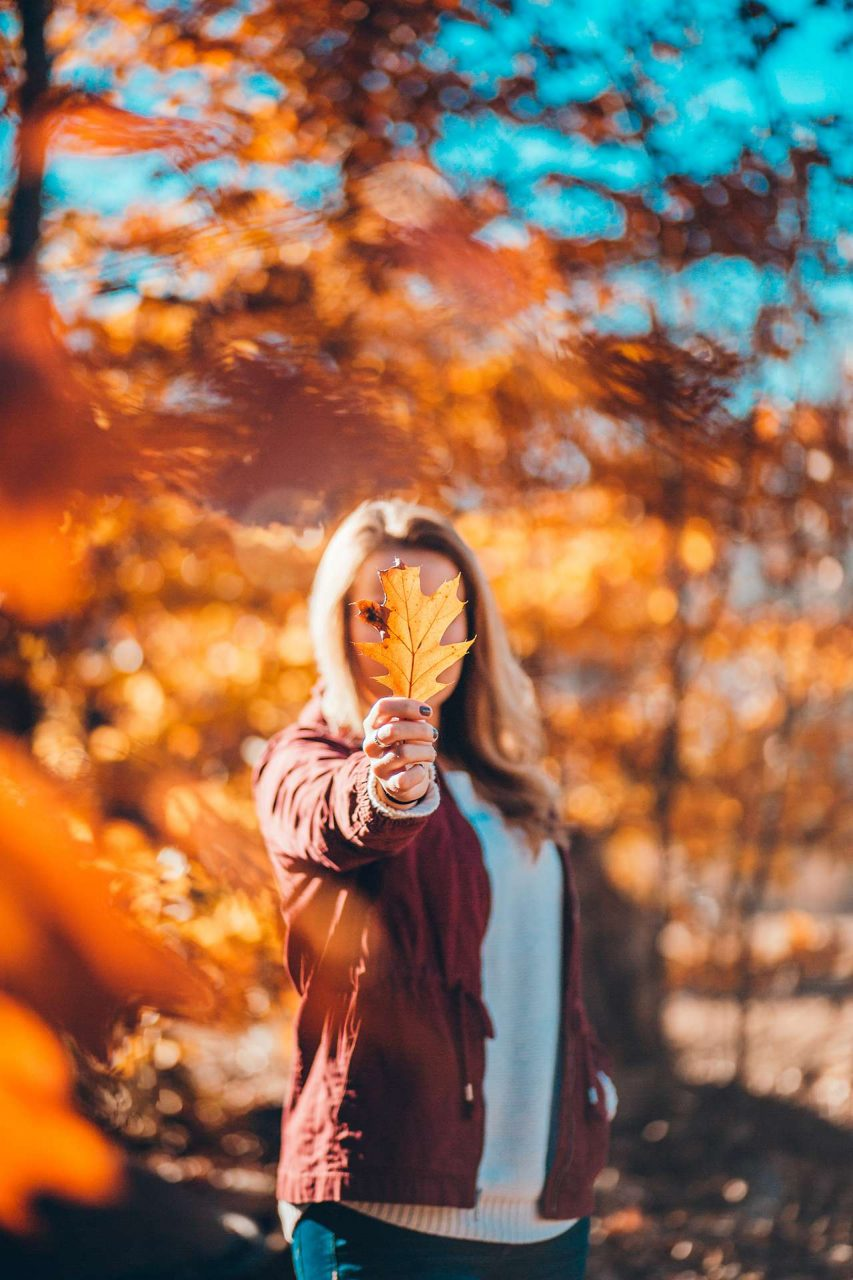 girl holding fall leaf
