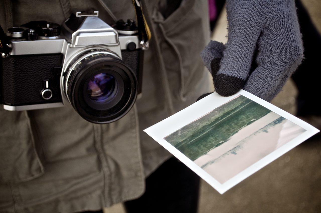 Classic camera with hand holding Polaroid photo