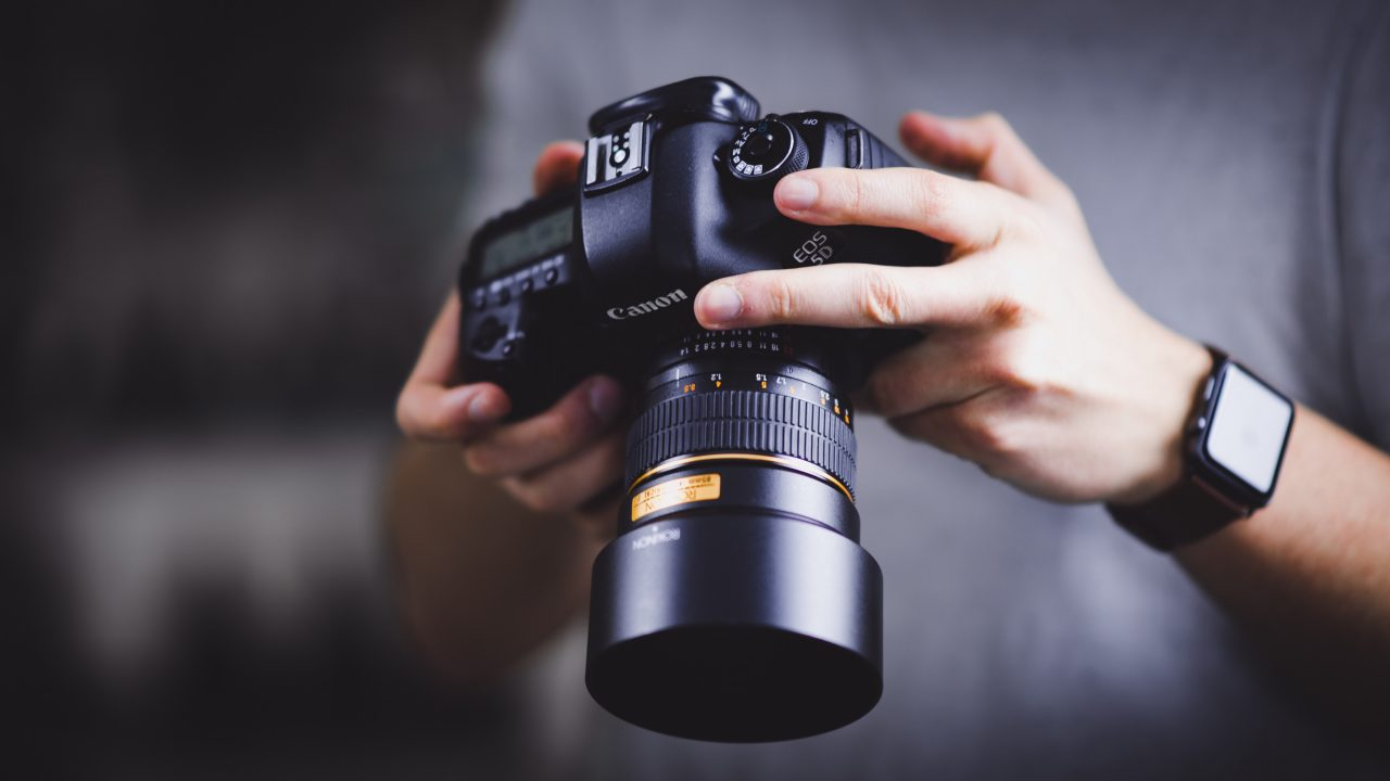 Hands holding Canon DSLR camera