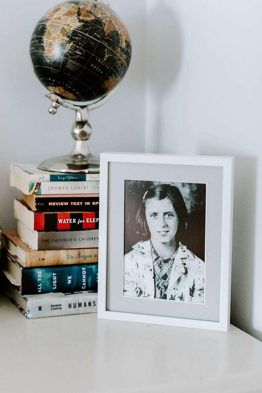 Photo framed next to globe and stack of books