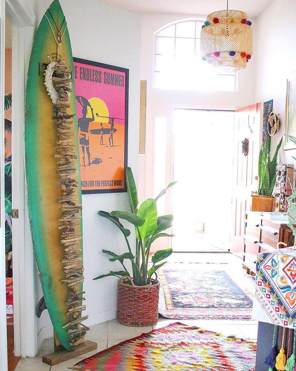 Boho-style hallway with surf board with Endless Summer poster in frame