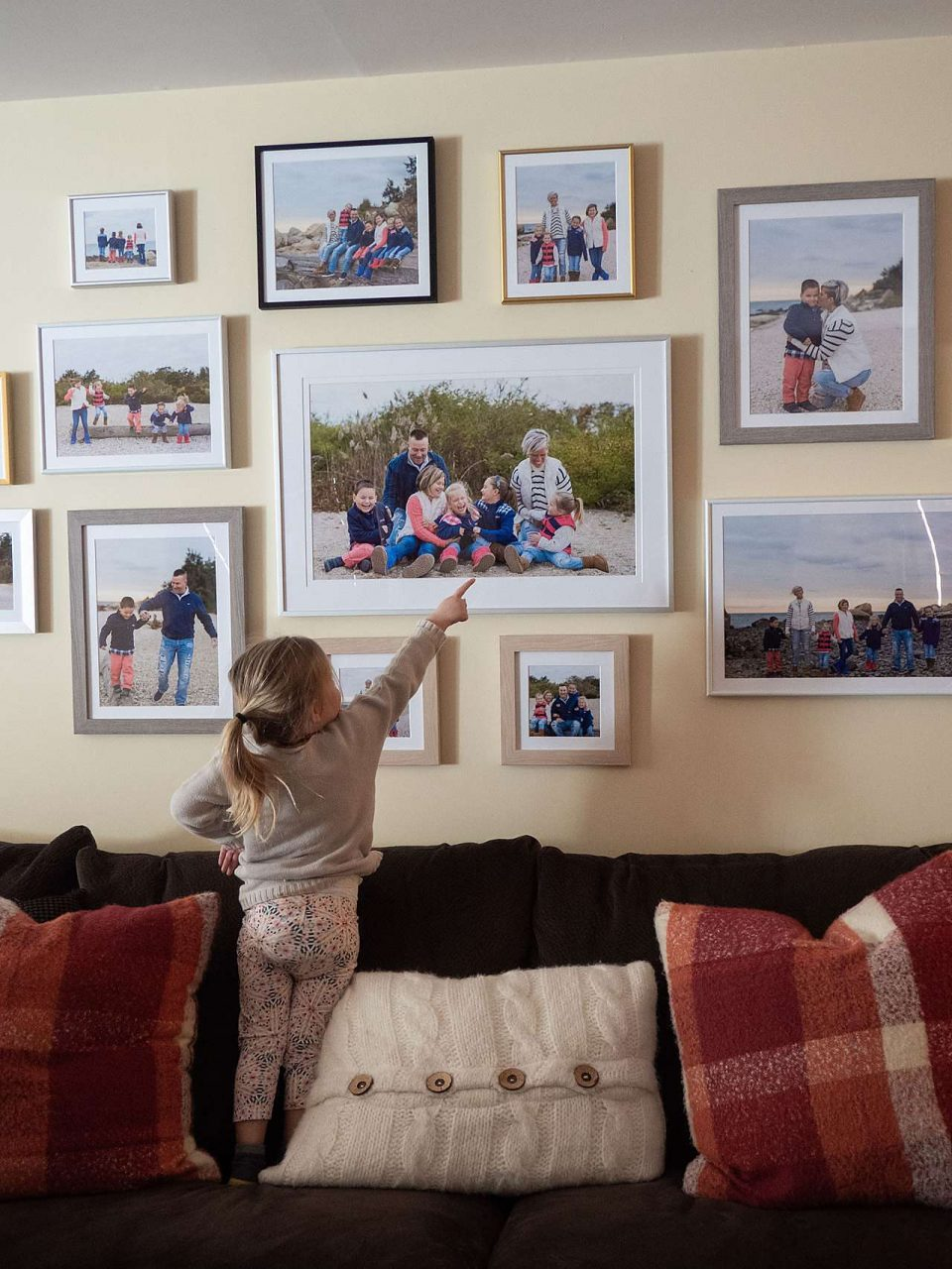 Family gallery wall with small child pointing