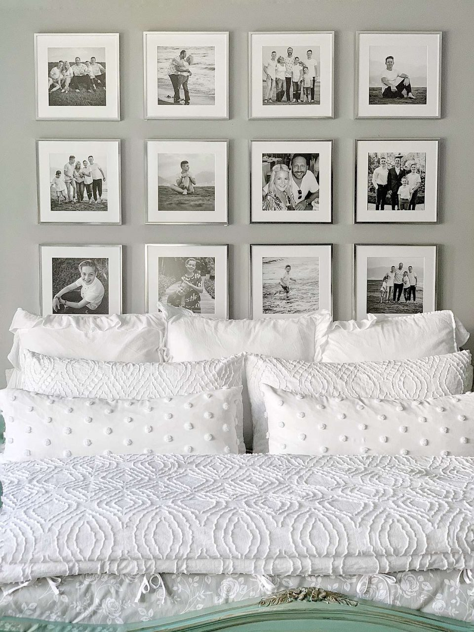 Silver picture frame gallery wall behind white bed