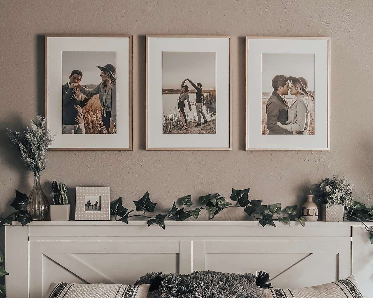 Triple picture frames above bed