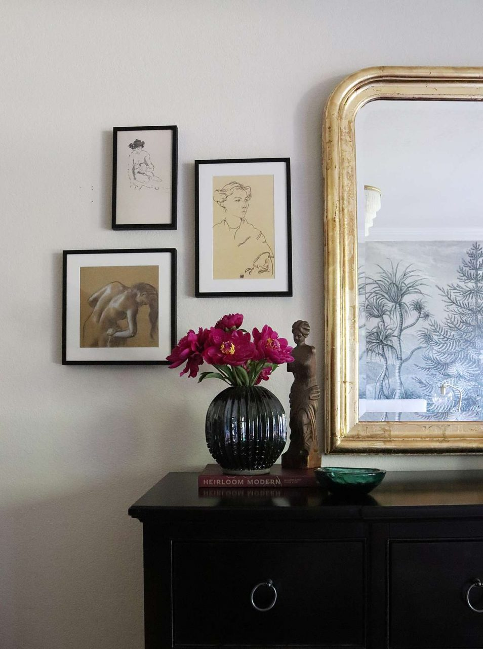 Offset triple picture frames next to mirror