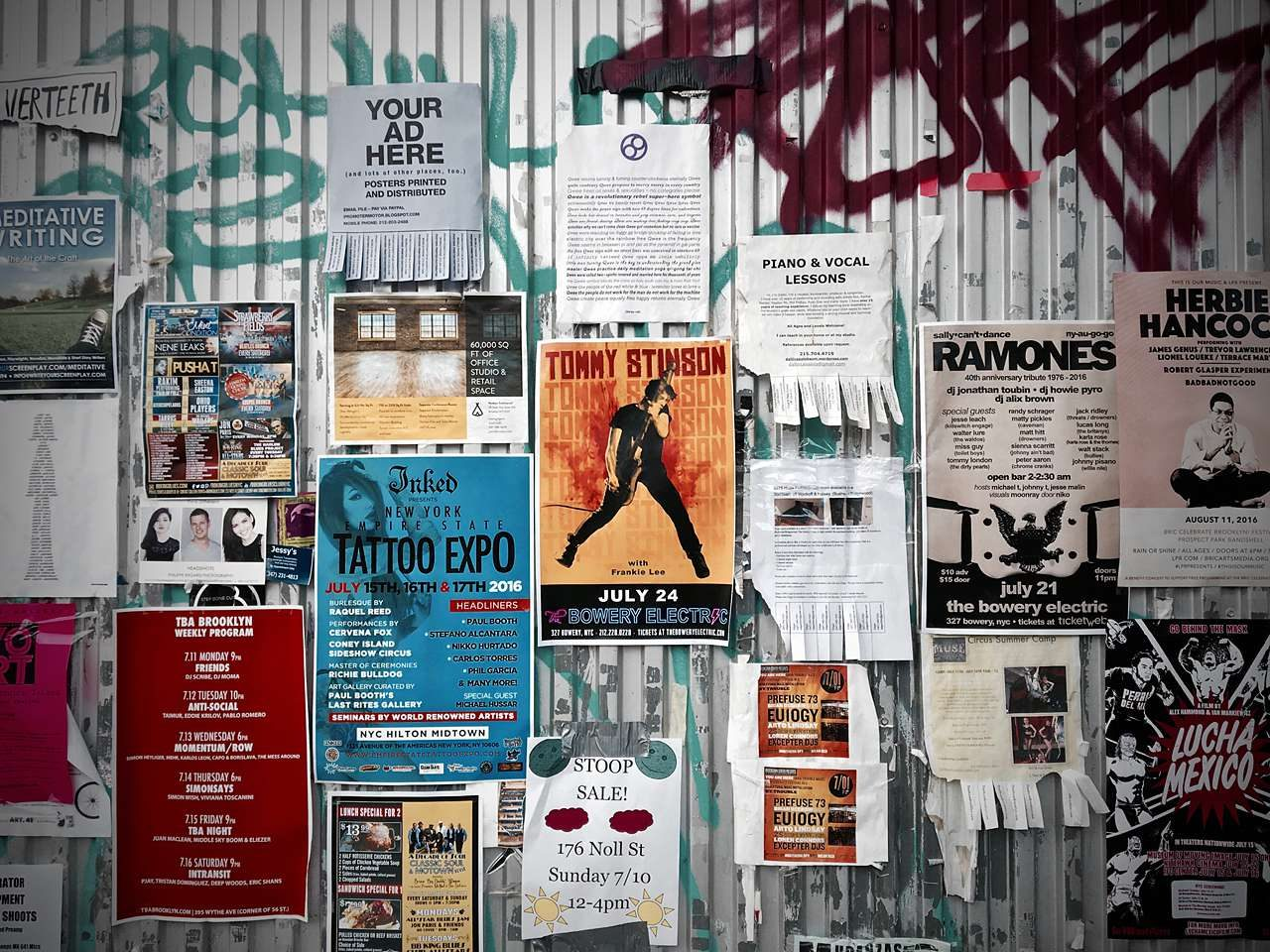 Printed flyers covering graffitied steel wall