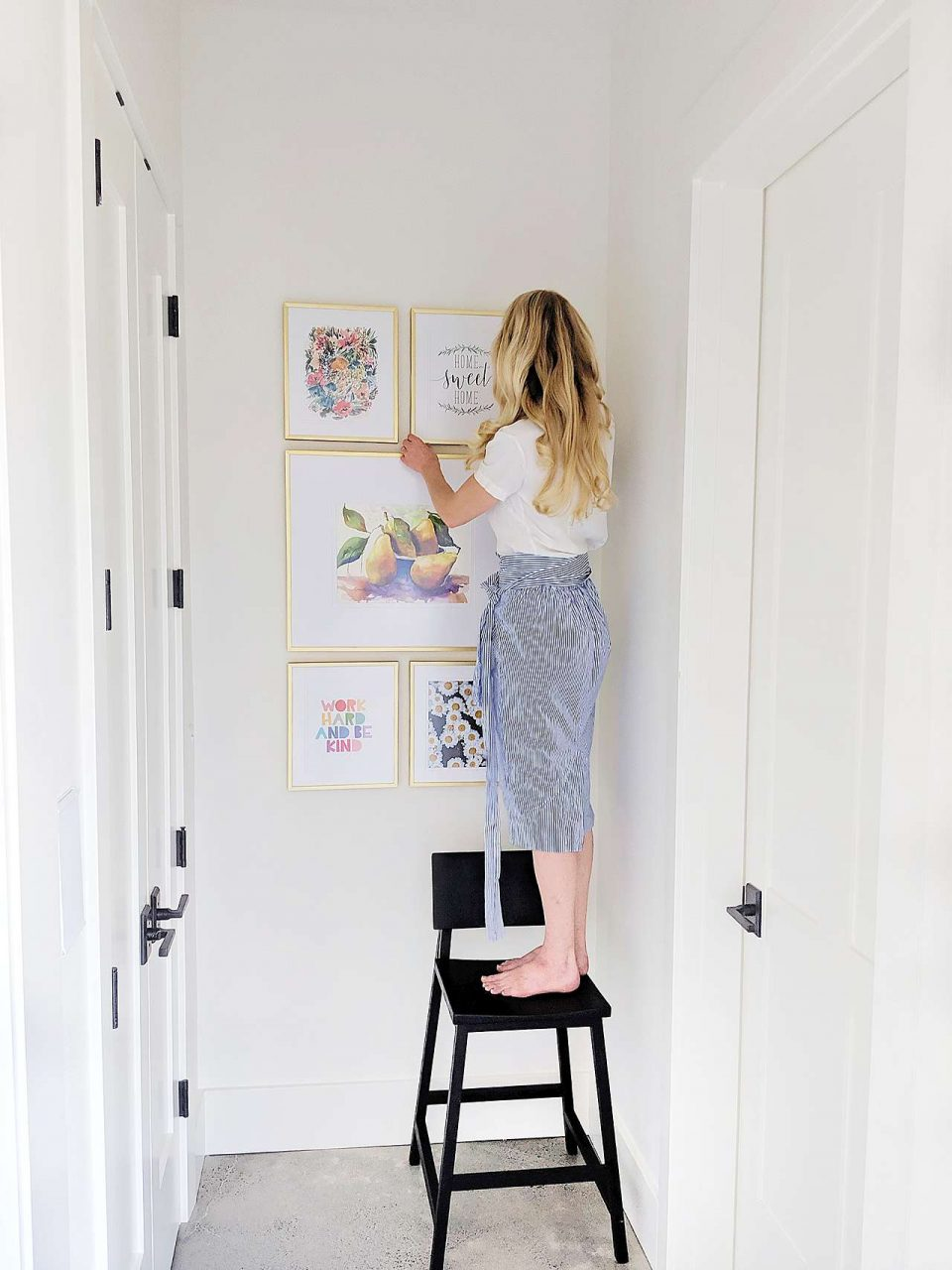 woman hanging gold picture frames