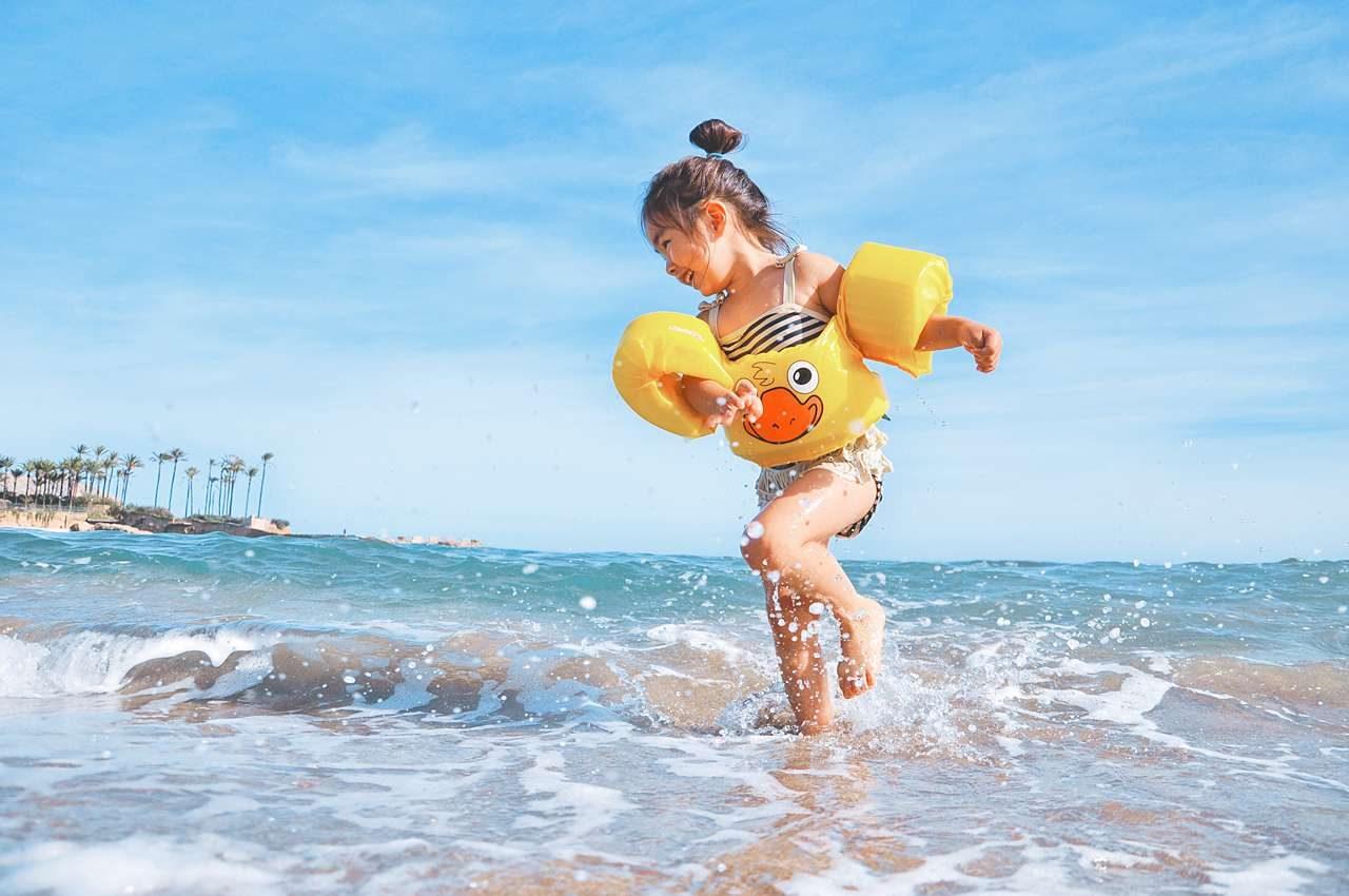 little girl splashing in ocean at beach