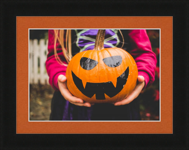 Fall art print - girl holding pumpkin painted like jack-o-lantern - Dayton in Black with Tangerine Matting