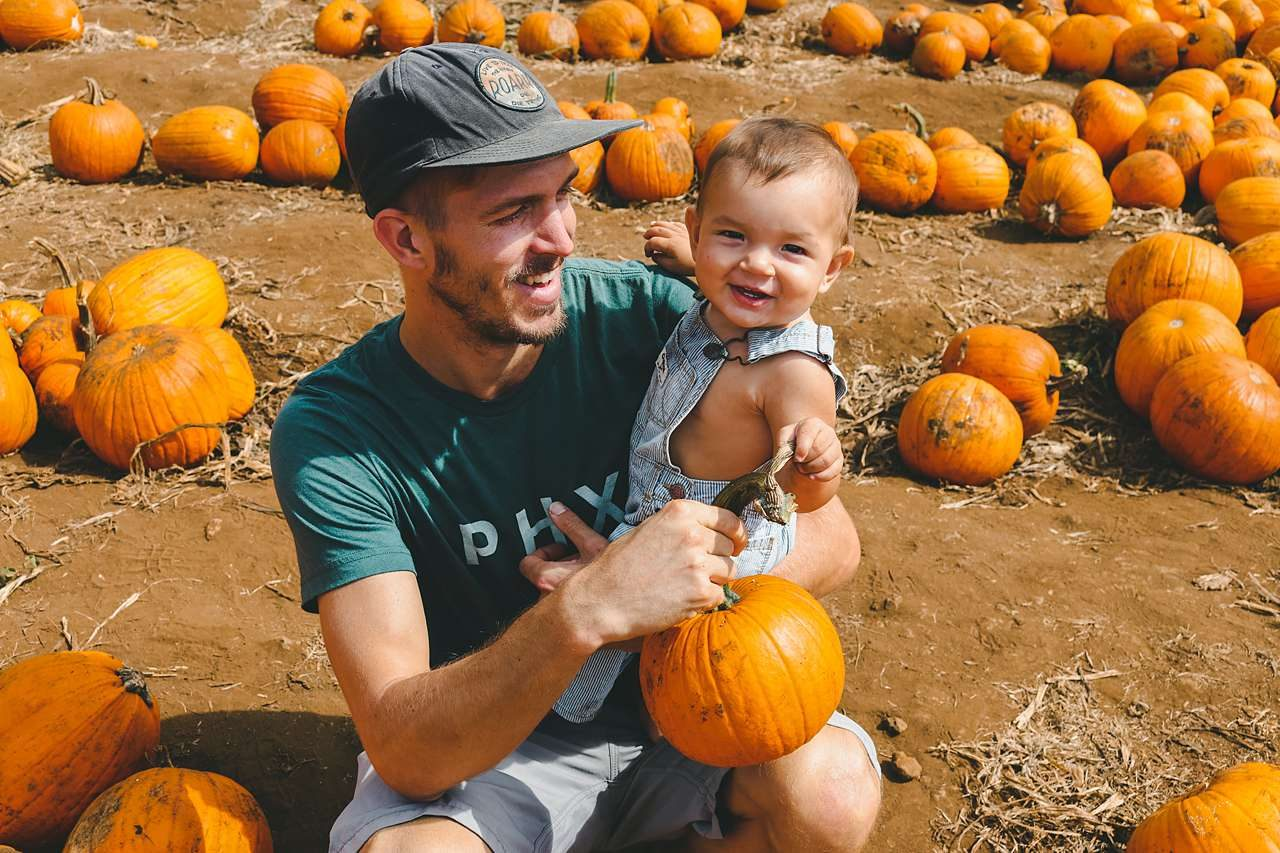 dad and son in pumpkin patch