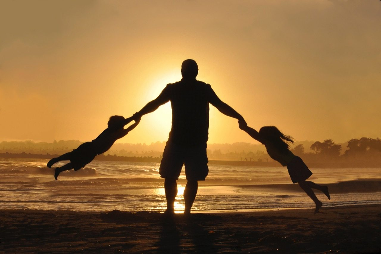 father and children silhouette on beach