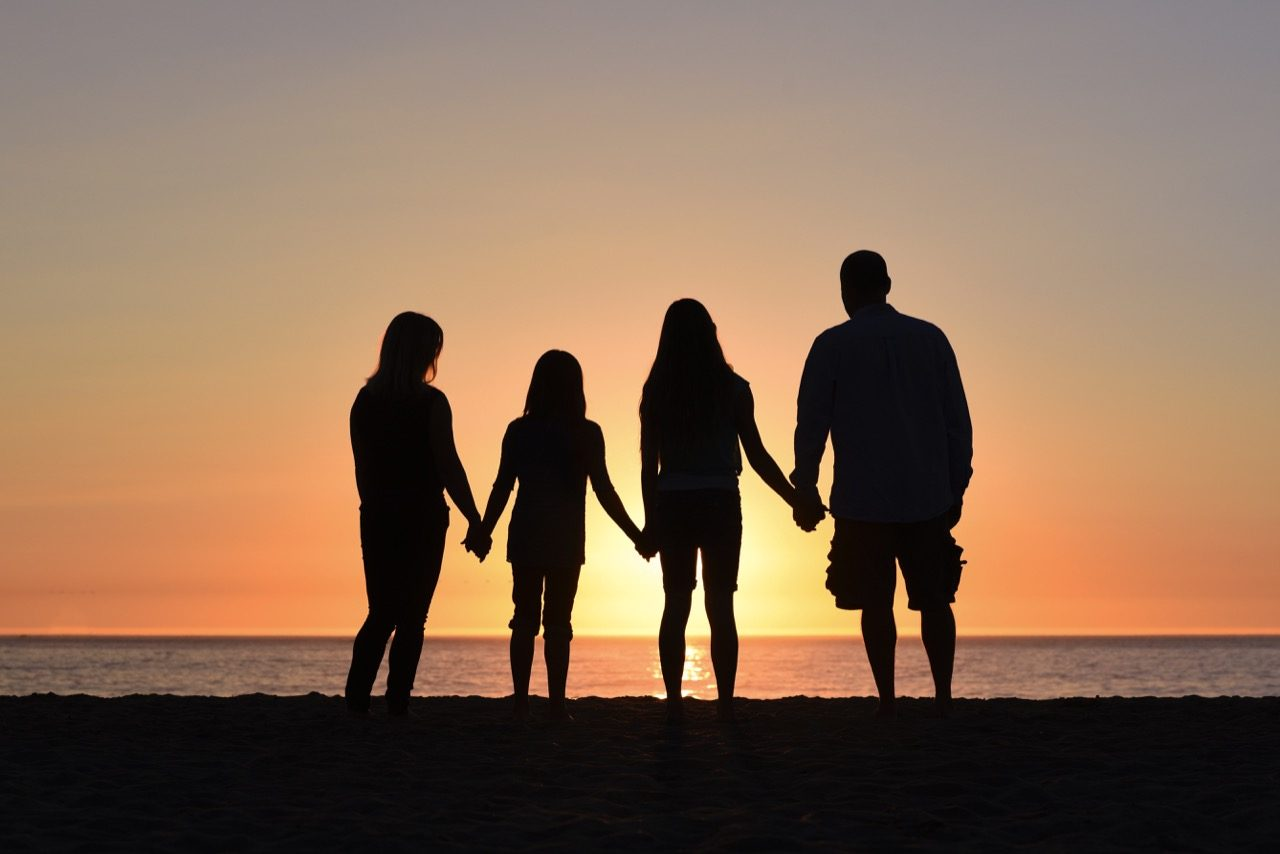 family silhouette on beach