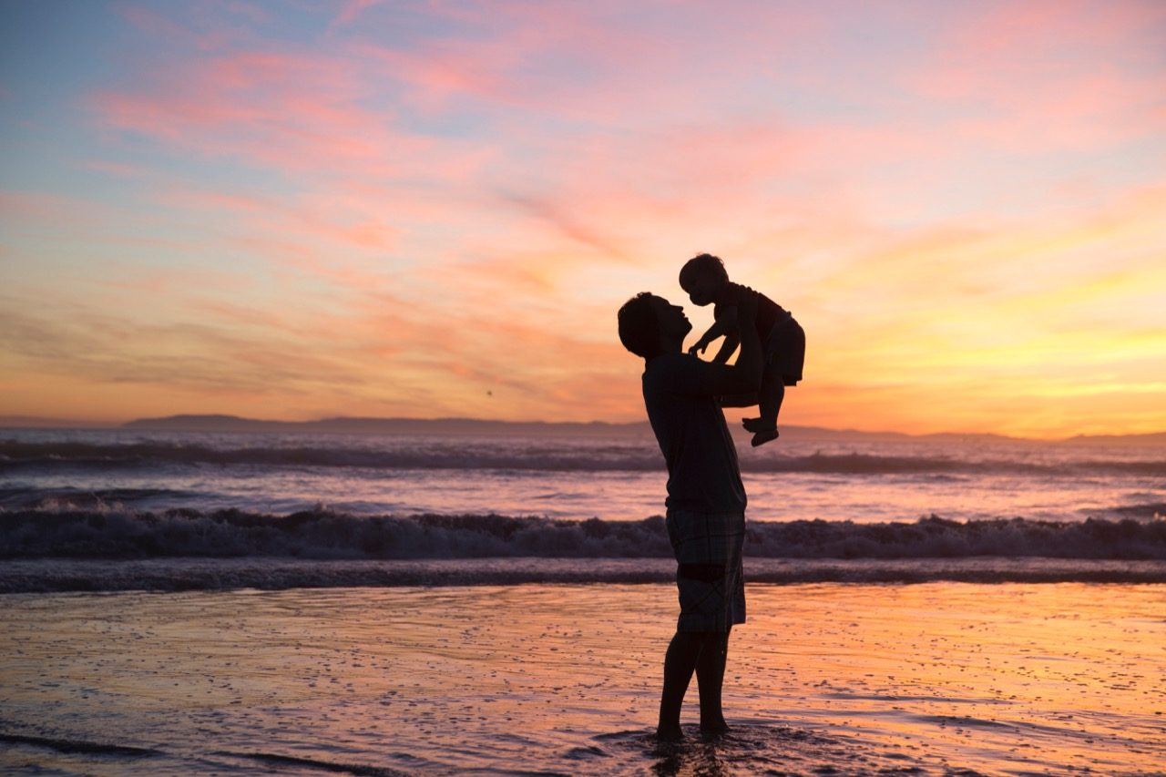 man and child silhouette on beach