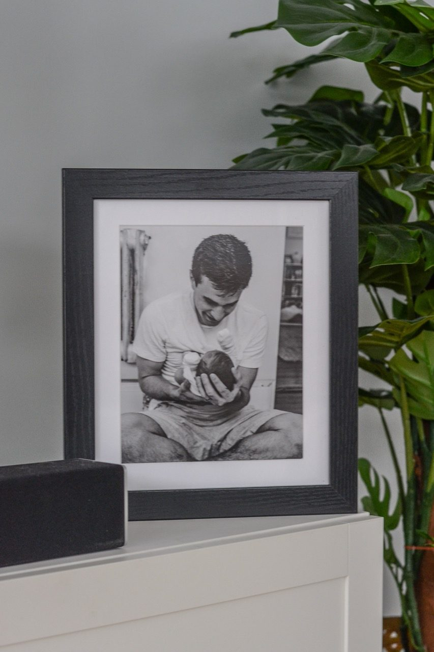 photo of dad holding newborn baby in black picture frame