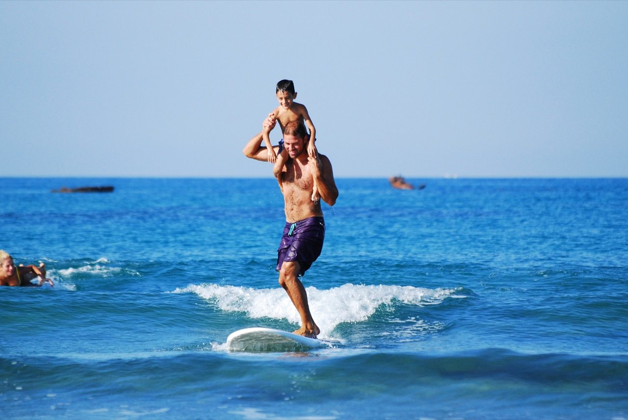 Dad carrying son on shoulders while surfing.