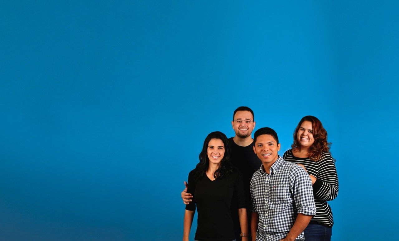 Family posing for picture in front of plain backdrop.