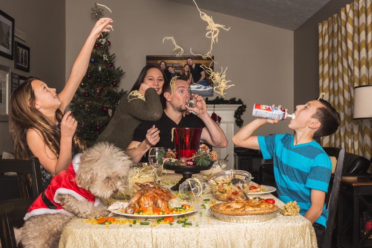 Goofy family holiday photo at dinner table.