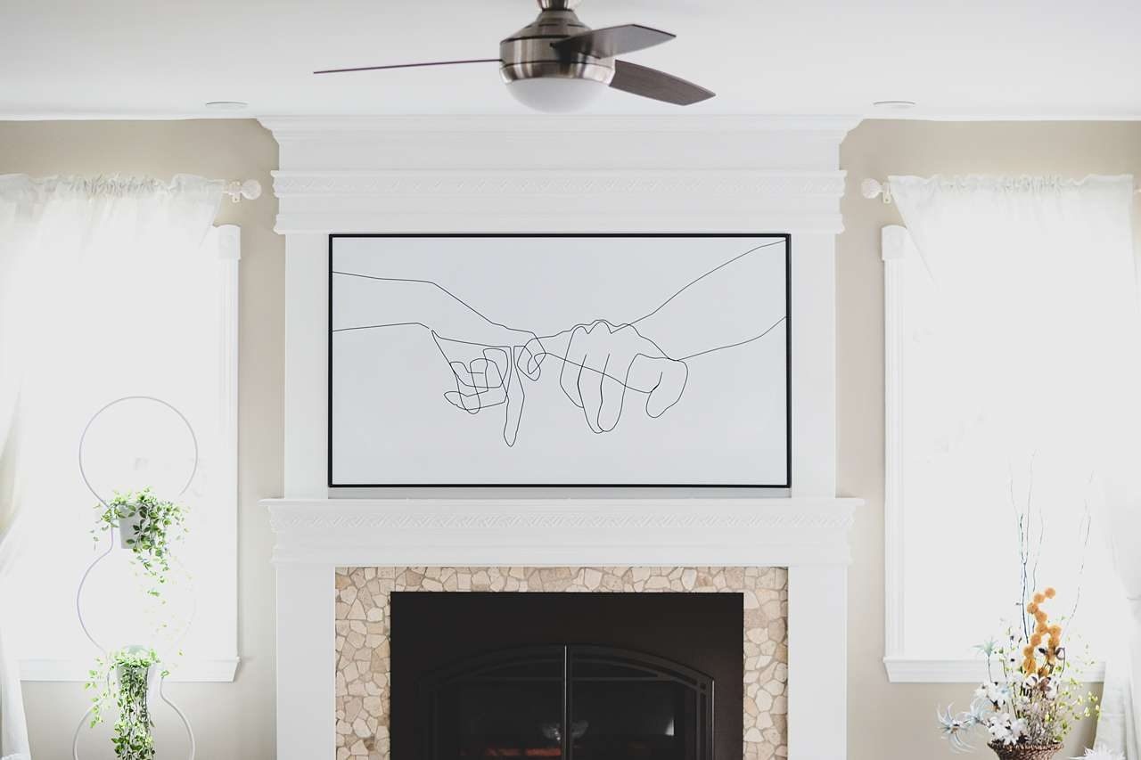 large framed wall piece above fireplace
