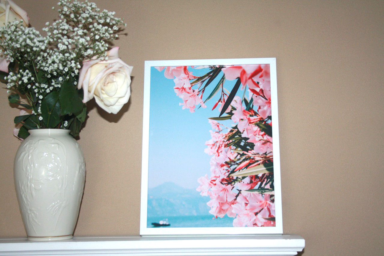 White framed photo on shelf with flowers