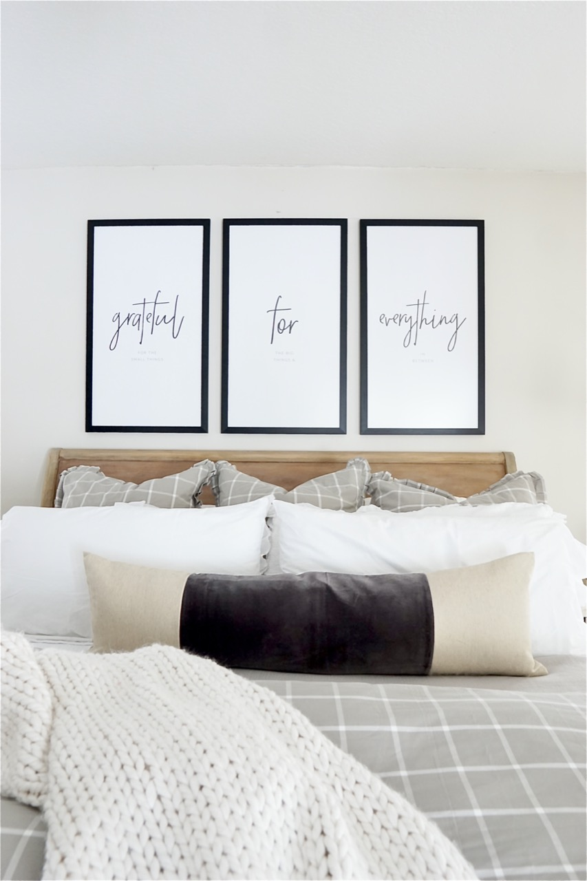 Three large picture frames above bed