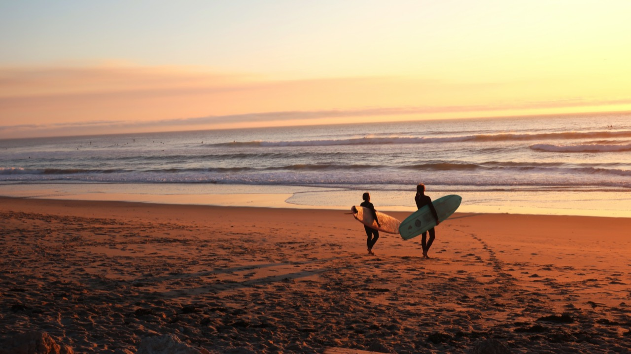 surfers walking to the water