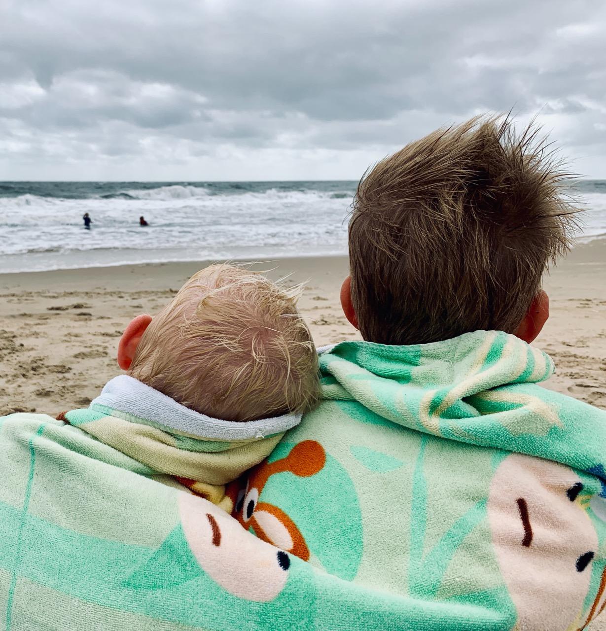 boys sitting on the beach