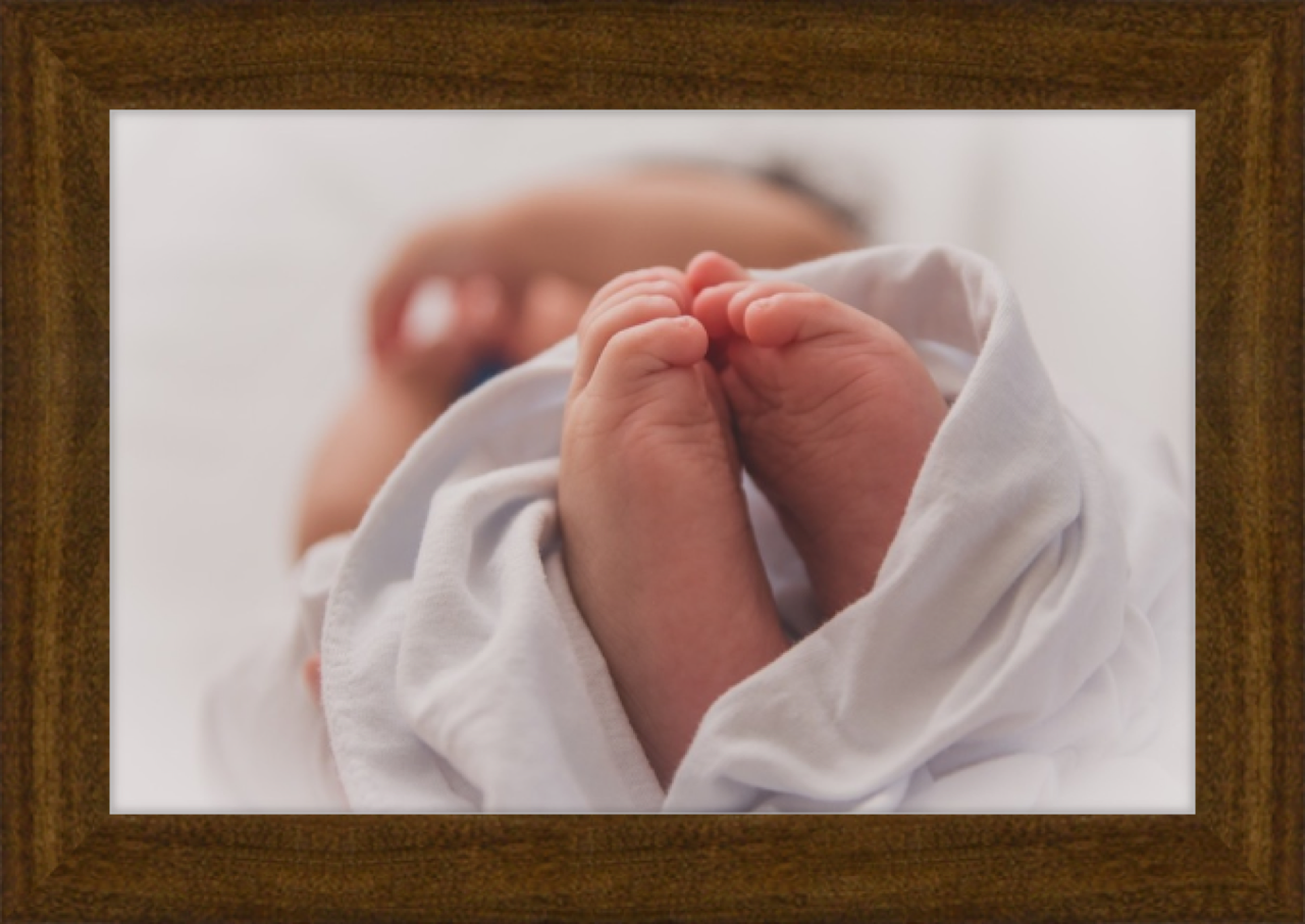 Dark wood frame around newborn photo